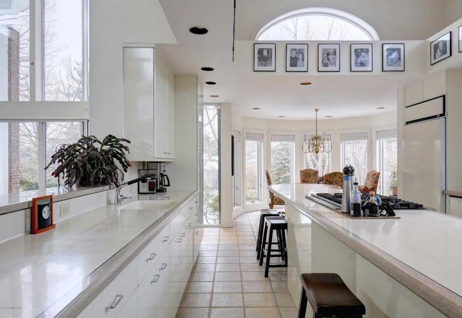 The combination of bright white countertops, paint, and cabinets with large windows on every well really modernizes the space.