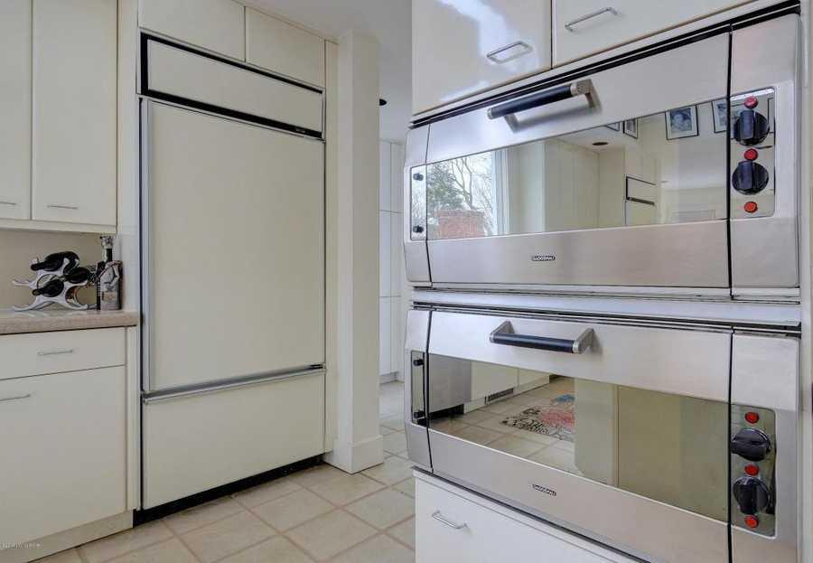 Close-up on the dual ovens and massive fridge.