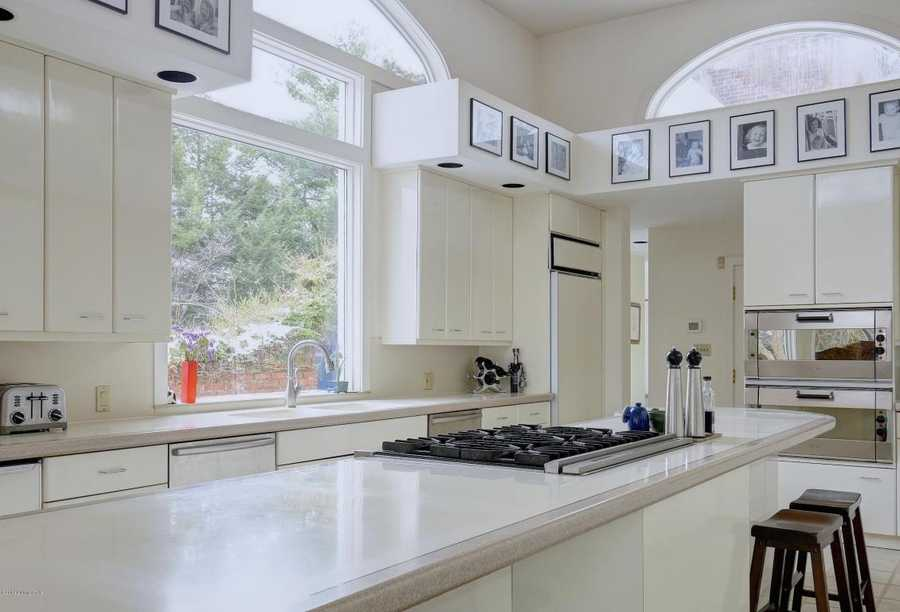 A large cooking island stretches the length of the kitchen and is framed by framed black and white art above the floorspace.