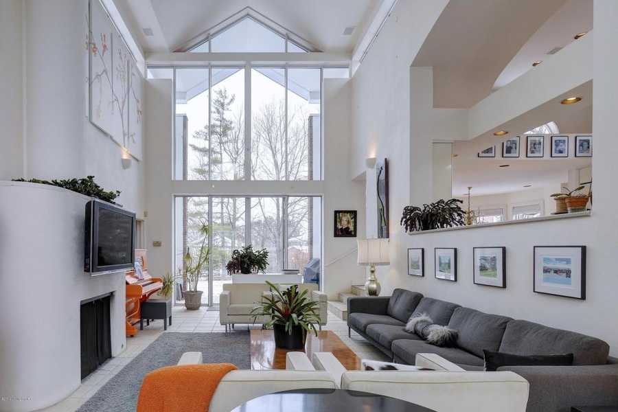 Sunlight streams through 25 foot high windows in a stunning great room which opens to a park-like fenced in back yard.