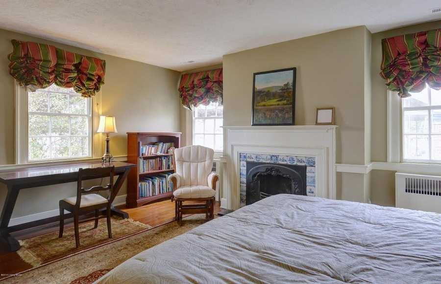 The rocking chair near the fireplace sets a cozy tone in this bedroom.