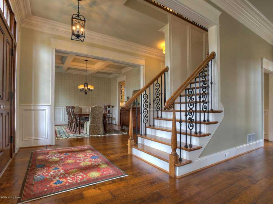 A foyer features vaulted ceilings, hardwood floors, and paneled walls.