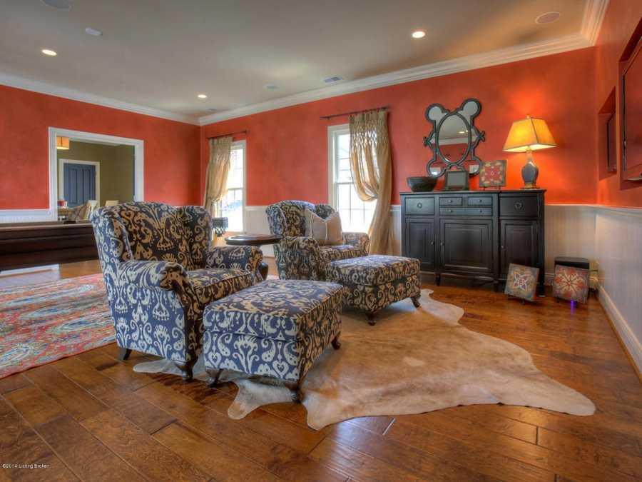 This quaint entertainment corner boasts a bold orange paint.