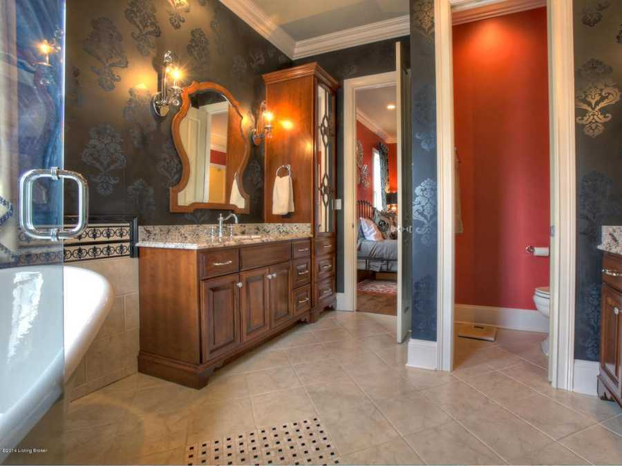 The en suite bathroom features an artistic wallpaper and beautiful mirror.