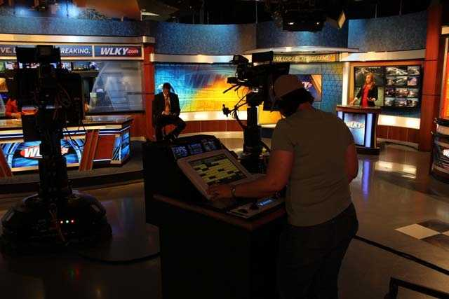 Floor director Amy Merrick sets the cameras to the correct positions to prepare for the next segment.