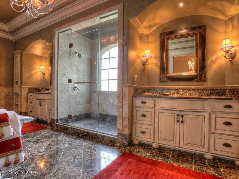 Large walk-in shower is the focal point of this luxurious bathroom. It stands between the dual vanity sinks.