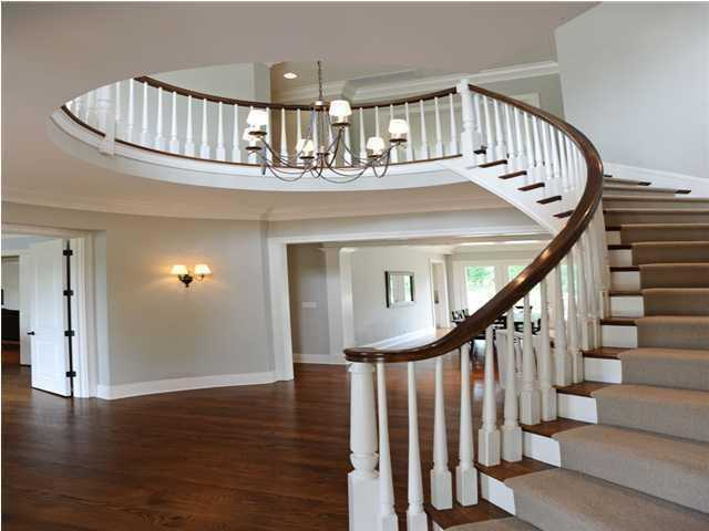 A dramatic oval entrance hall with curved staircase makes a dramatic statement.