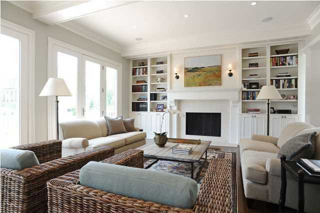 The living room features a fresh design and amazing views of the deep rear yard. It also boasts a white wooden shelving unit built around the modern fireplace, recessed lighting and tall french doors.