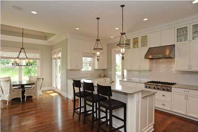 The open gourmet kitchen includes a gas grill and tiered cooking island for bar seating and eating.