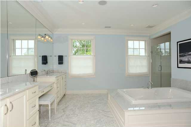 Luxurious master bathroom boasts a sprawling spa tub, marble tiled floors, dual vanities, and step-in shower.