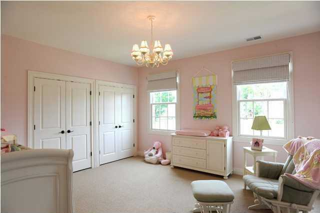 This room currently serves as a nursery and boasts a timeless chandelier.
