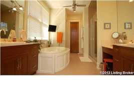 The master bathroom features a large spa tub.
