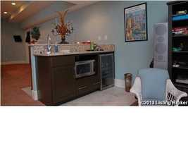 Basement's bar includes a microwave and wine cooler.