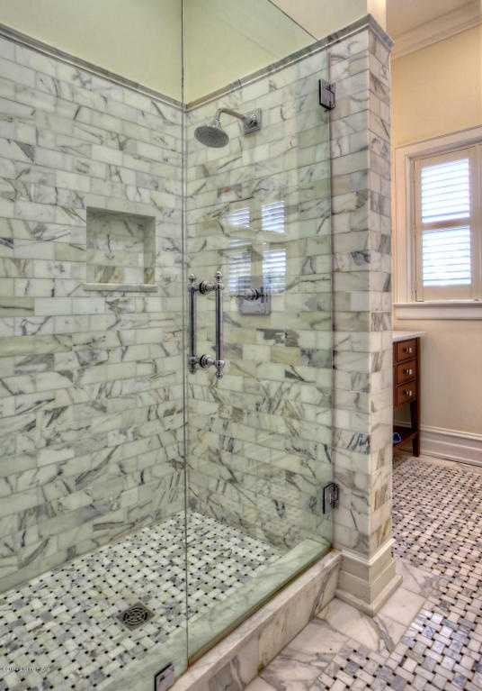 """Even the floor in the master bathroom features a """"woven"""" marble design."""