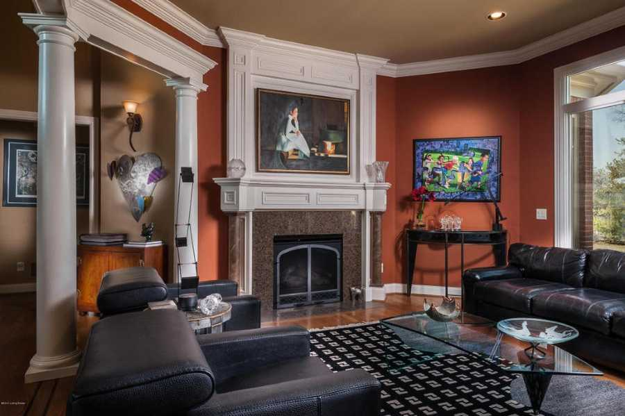 The formal living room features a contemporary, artsy theme, lovely recessed lighting, fireplace, and roman-style pillars.