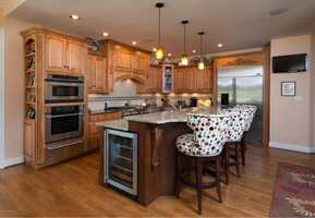 This wide-open kitchen features a large granite-topped cooking island with a built-in wine cooler&#x3B; which ironically is the first sign that this kitchen is made for entertaining.