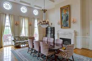 The traditional room also has a fireplace, chandelier, and is well lit.