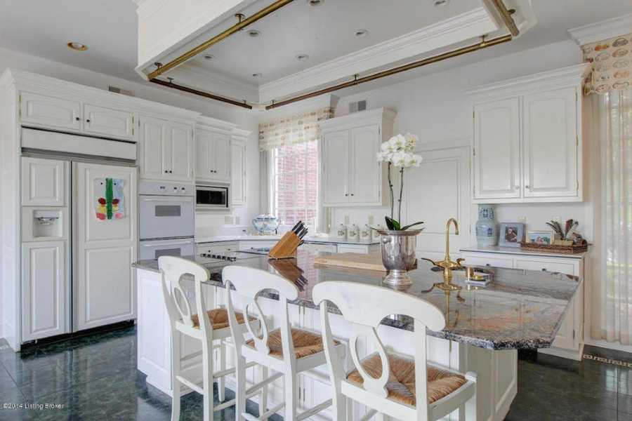 Stunning kitchen boasts matching marble countertops and floors.