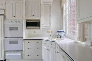 Top-of-line appliances in white to match the cabinets.