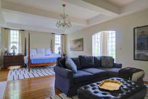 Master bedroom features lovely floor-to-ceiling windows and a sitting area.