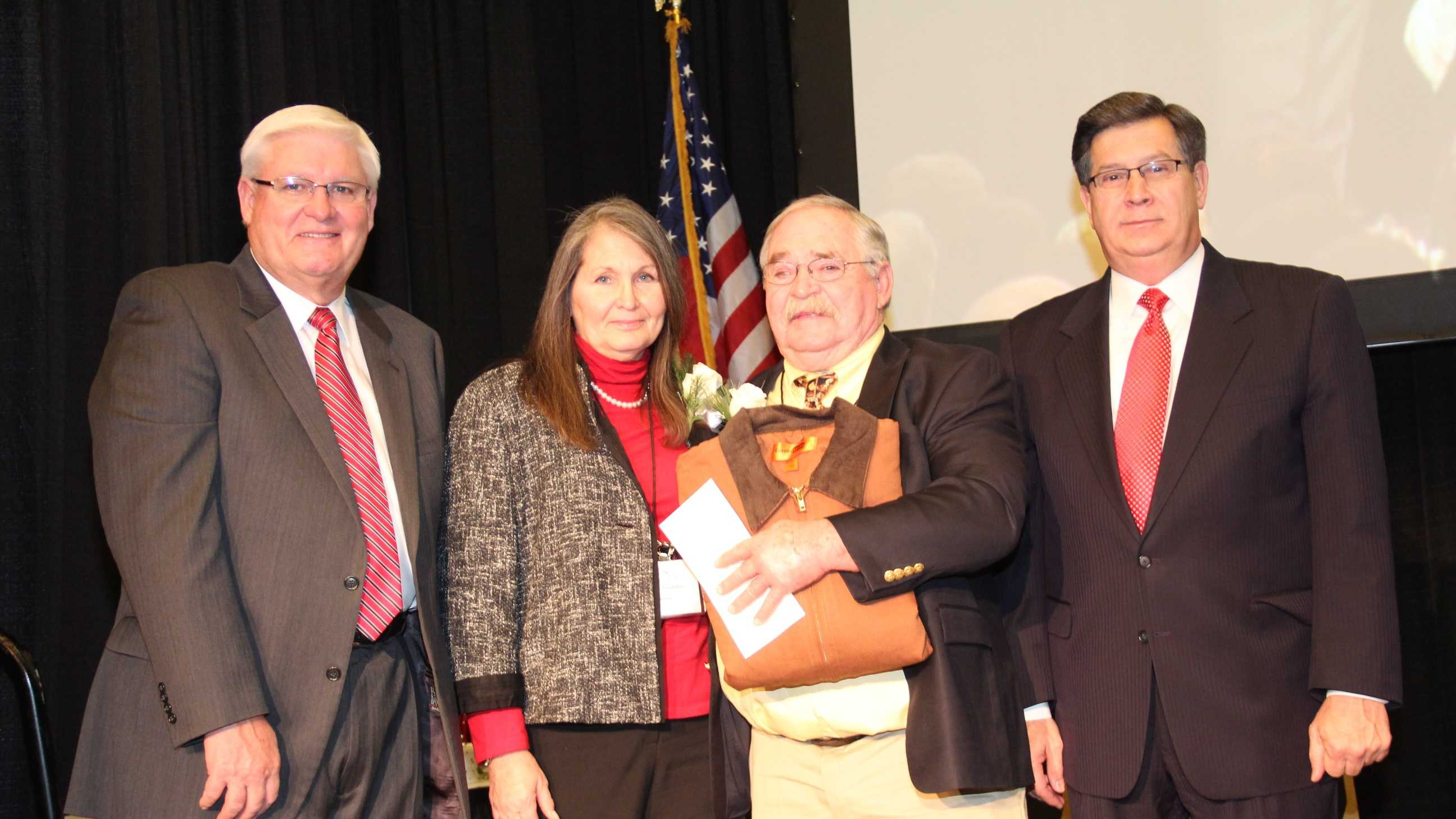 "Jack Trumbo and his wife, Gwyn, receiving his ""Farmer of the Year"" award from Kentucky Farm Bureau in December 2014. Presenting the award are KFB President Mark Haney (left) and KFB Executive Vice President David Beck (right)."