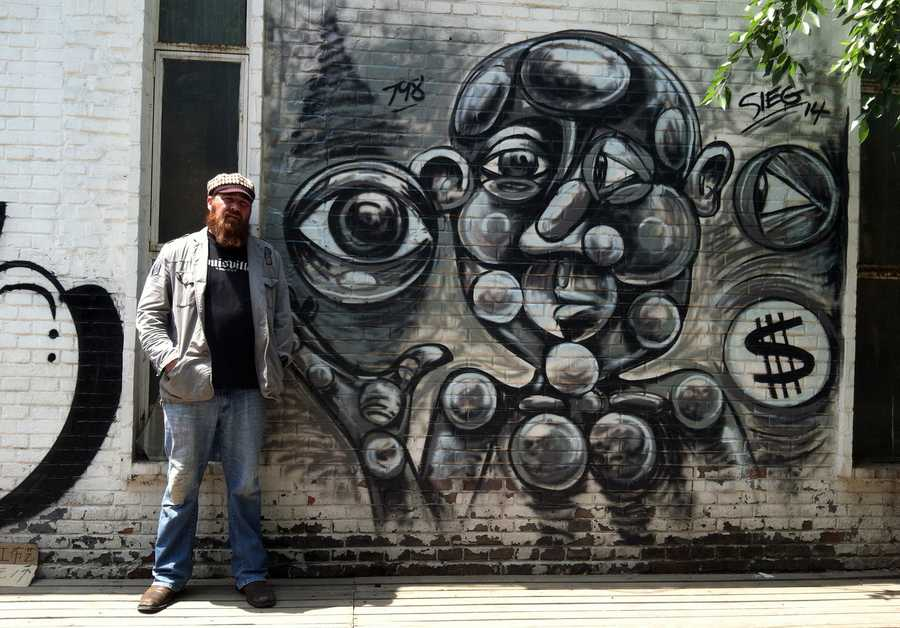 Artist Wilfred E. Sieg III with his work in China