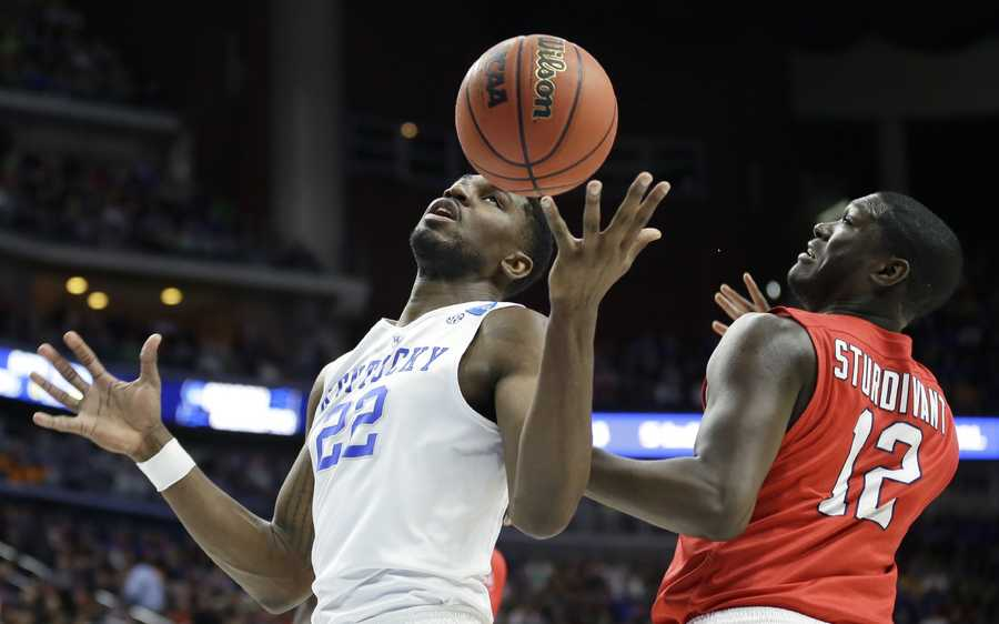 Kentucky forward Alex Poythress, left, loses the ball in front of Stony Brook forward Tyrell Sturdivant, right, while driving to the basket during the first half of a first-round men's college basketball game in the NCAA Tournament, Thursday, March 17, 2016, in Des Moines, Iowa.