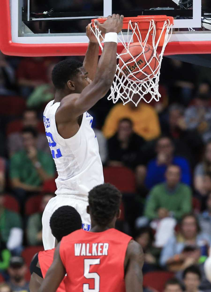 Kentucky's Alex Poythress (22) dunks with Stony Brook's Ahmad Walker (5) watching, during a first-round men's college basketball game in the NCAA Tournament in Des Moines, Iowa, Thursday, March 17, 2016.
