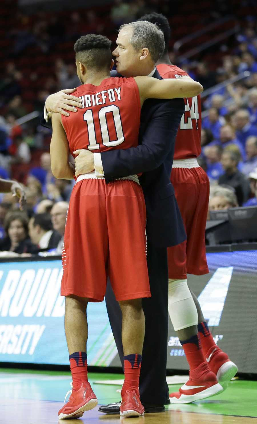 Stony Brook guard Carson Puriefoy (10) gets a hug from coach Steve Pikiell at the end of a first-round men's college basketball game against Kentucky in the NCAA Tournament, Thursday, March 17, 2016, in Des Moines, Iowa. Kentucky won 85-57.
