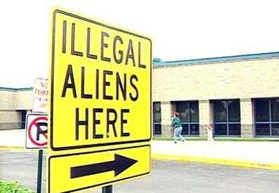 A sign says 'Illegal Aliens Here'