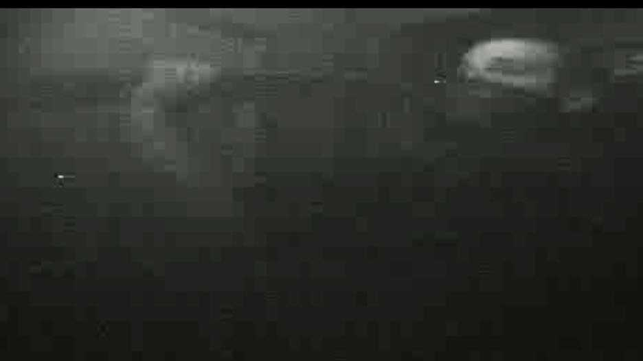 A grainy image of a man removing a board from a door. The image was captured by a security camera installed by deputies after three previous burglaries.