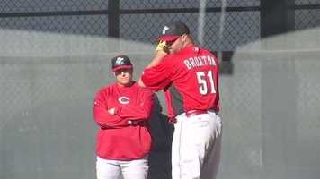 Jonathan Broxton gets ready for the season as pitching coach Bryan Price watches.