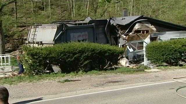 A woman escaped with cuts and scrapes when a garbage truck trashed her home Monday morning.