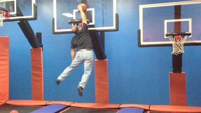 WLWT News 5's Mark Hauss attempts a dunk with the help of trampolines.