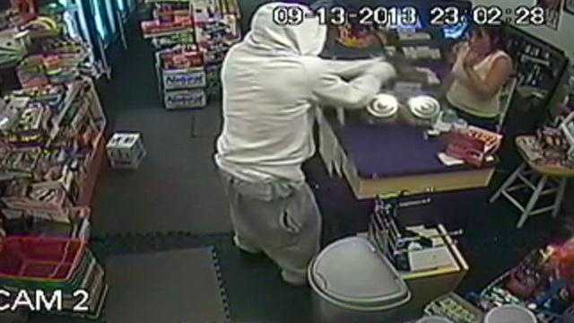 A clerk at the International Market cowered in fear as two masked men robbed the store.