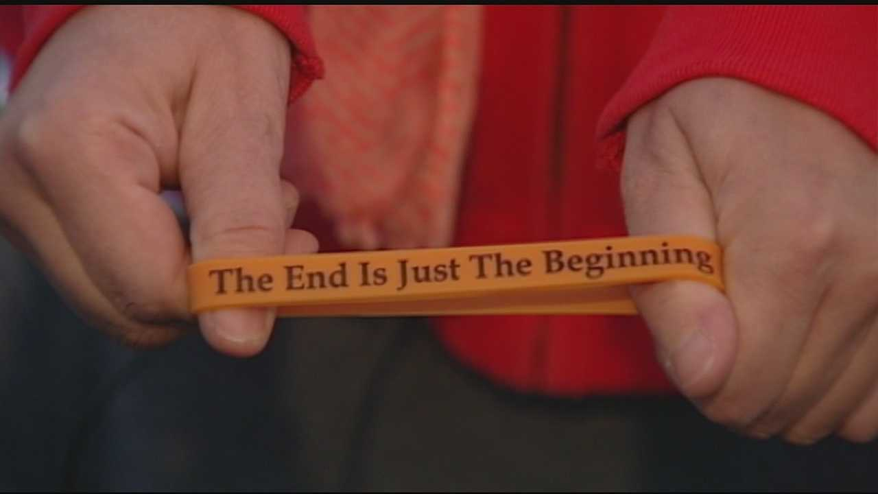 "It is a black silicone rubber bracelet with red lettering that says, ""The End is Just the Beginning."""