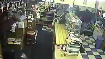 Clerk appears at left with vacuum as robber turns to run.