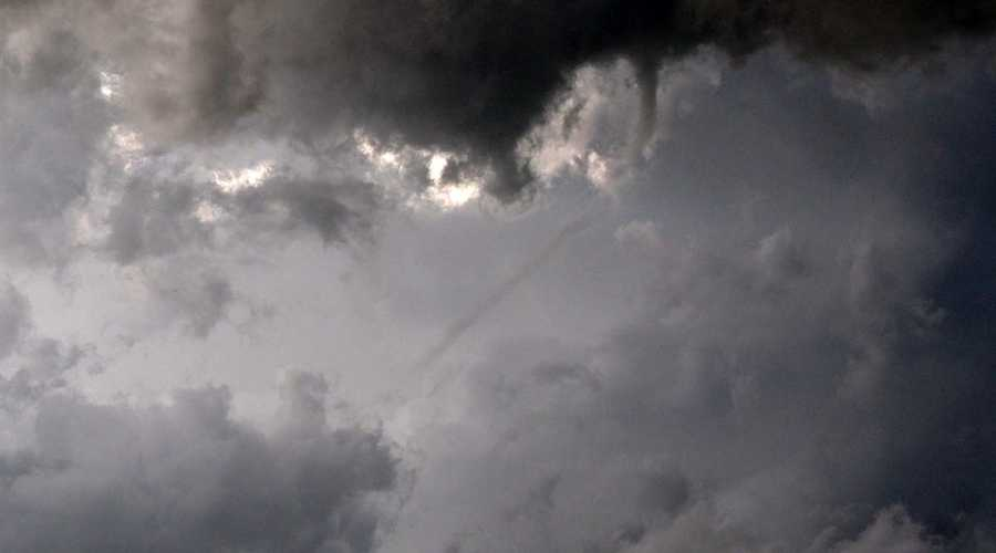 Thin wispy funnel cloud reaches from upper right to lower left