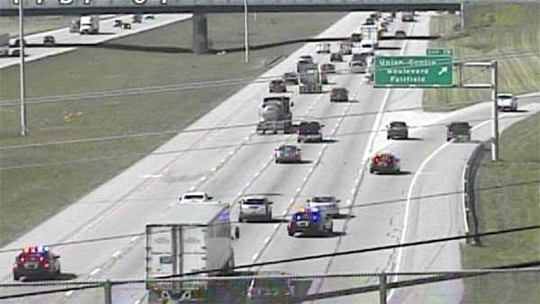 The black pickup exits I-75 SB at Union Centre with police cruisers in pursuit.