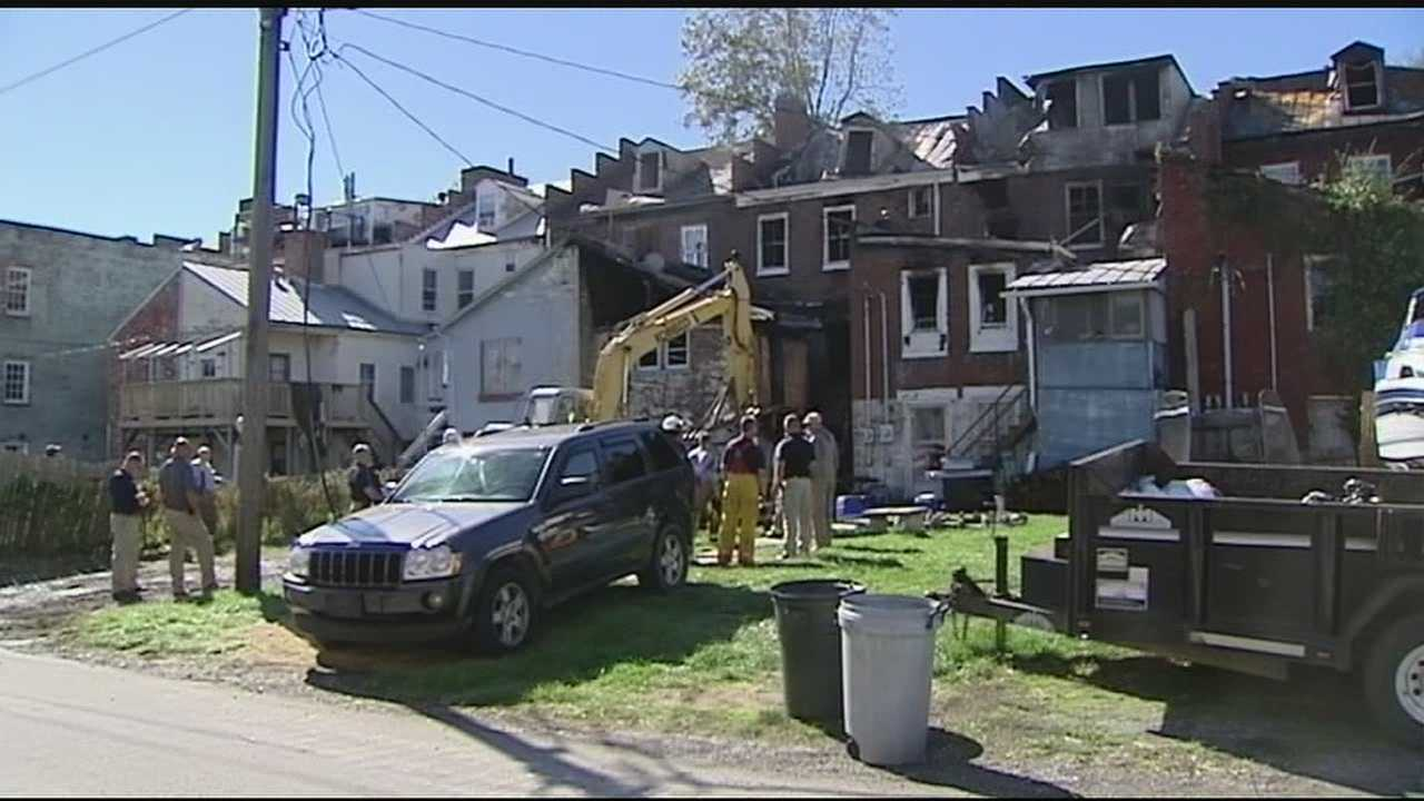 The fire appeared to start on the back porch of a row house and spread quickly, killing a woman, three of her children and a neighbor, authorities said.