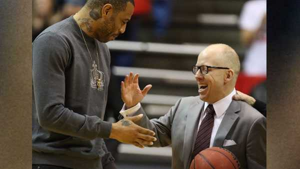 Cincinnati head coach Mick Cronin, right, is presented the game ball by former Cincinnati and NBA player, Kenyon Martin, following Cronin's 200th career win with Cincinnati, after a 97-75 defeat of Tulane in an NCAA college basketball game Sunday, Jan. 24, 2016, in Cincinnati. (AP Photo/Gary Landers)