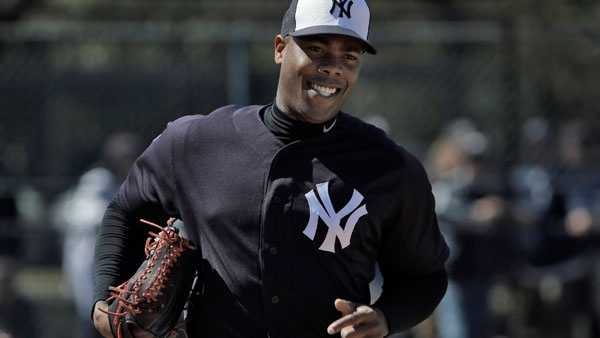 New York Yankees pitcher Aroldis Chapman smiles as he runs pickoff drills during a spring training baseball workout Friday, Feb. 19, 2016, in Tampa, Fla.