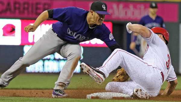 Colorado Rockies third baseman Nolan Arenado, left, tags out Cincinnati Reds' Jay Bruce, attempting a triple, during the fifth inning of a baseball game, Monday, April 18, 2016, in Cincinnati. (AP Photo/Gary Landers)