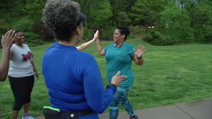 A woman in Black Girls Run Cincinnati, an organization aimed at battling obesity in the black community, finishes her run to high-fives from other club members. The group will participate in the 2016 Flying Pig.