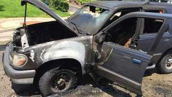 Two men escaped this car without injury after it exploded and caught fire on Eden Park Drive Sunday afternoon.