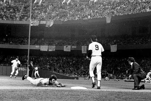 Pete Rose of the Cincinnati Reds slides to third during eighth inning of game three in World Series action against the New York Yankees at Yankee Stadium in the Bronx, N.Y., on Oct. 20, 1976. At right is Yankees player Graig Nettles (9). The Reds defeated the Yankees, 6-2.