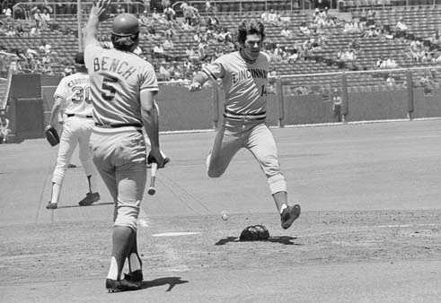 Pete Rose who rapped out his 2,000th career hit during this series, June 21, 1973, in San Francisco flys across the plate with the Cincinnati Reds' sixth run in the fourth inning yesterday as Johnny Bench whose spectacular catch robbed the San Francisco Giants Bobby Bonds of a tying homer in the fourth holds a runner at third. Giant's pitcher Don Carrithers, the pitcher of record in the 7-5 Giant loss watches at left.