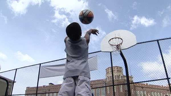 A boy plays basketball at the court at Main Street and Clifton Avenue in Over-The-Rhine in Cincinnati.