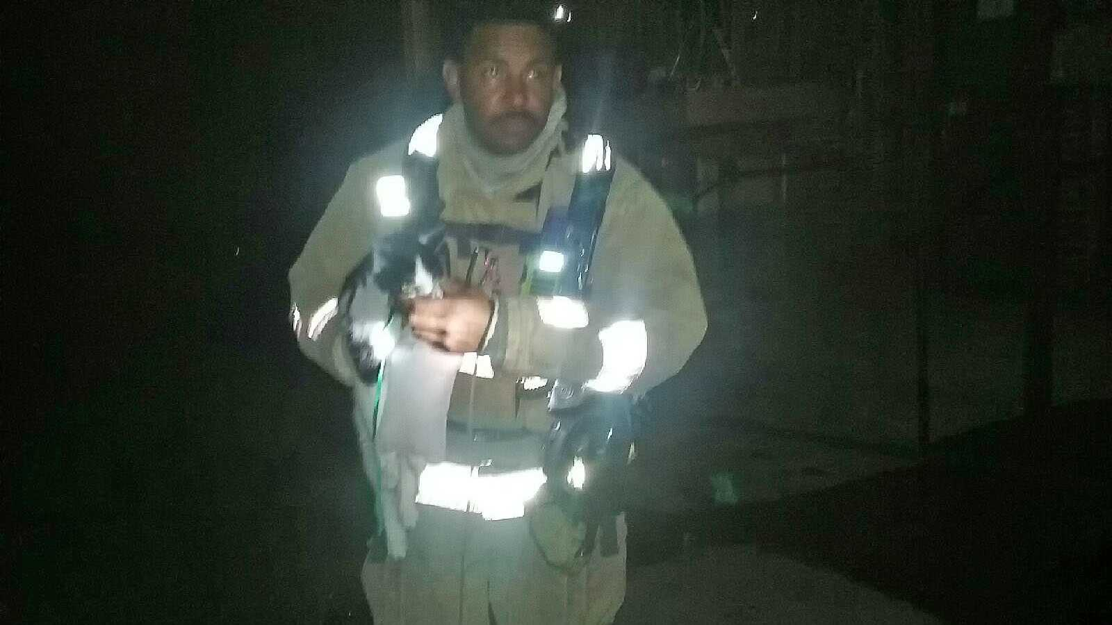 Firefighter carries cat out of apartment building, using oxygen mask to help it breathe.