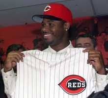 Ken Griffey Jr. holds up a Cincinnati Reds jersey during a news conference at Cinergy Field in Cincinnati, Thursday, Feb. 10, 2000. Following three months of often deadlocked trade talks, the Reds reunited Ken Griffey Jr. with his father and his hometown Thursday by sending four players to the Seattle Mariners.